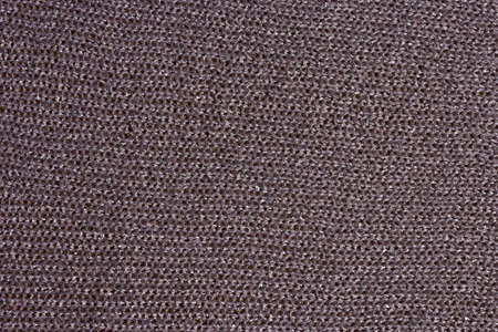 Knitted mauve background. Knitted purple textiles for text. The texture of a wool sweater. Hand knitting. Machine knitting. Purple, violet, lavender.