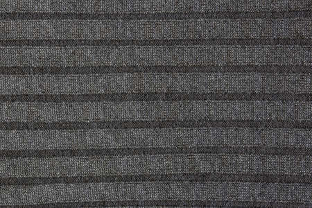 Repeating Machine Knitting Texture of Sweater. Knitted Background. Cable knit background texture in gray tones. Knitting textile for text. Fabric texture of woolen sweater with stripe.