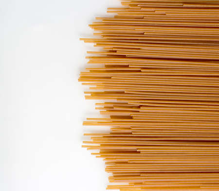 Italian spaghetti in dark color design with copy space, a flat lay of many pasta, shot from above on a white background with a place for text. Texture of pasta macaroni from a solid wheat variety.