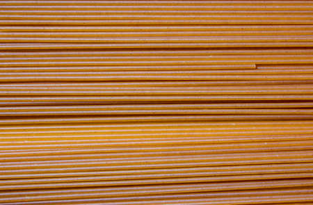 The background is dark-colored Italian spaghetti. Italian Macaroni Pasta raw food background or texture close up. Italian pasta made of durum wheat. High angle view spaghetti. Standard-Bild