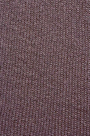 Knitted mauve background. Knitted purple textiles for text. The texture of a wool sweater. Purple, violet, lavender.