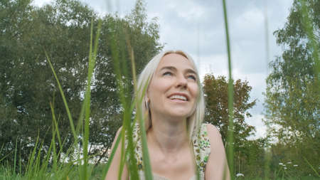 A young smiling beautiful woman in a light dress lies on the grass and looks at the sky against the background of trees.