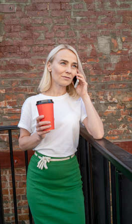 A beautiful girl talks on her mobile phone during lunchtime and drinks coffee from a red cup. A young girl drinks coffee from a green paper cup and looks away.