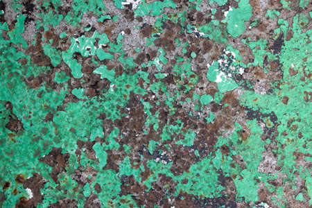 The metal wall is painted with green paint, the old paint is blown away, rust rust from under the paint. Peeling green paint from metal. Rusty Metal Surface With Peeling Paints. 免版税图像