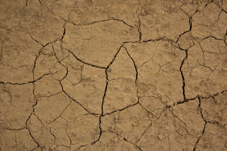 Dry and cracked earth. Dried yellow soil crack. Environmental problem drought and thirst. The texture of the ground dried up in cracks. Dry cracked soil earth background texture. Vintage, nature Standard-Bild
