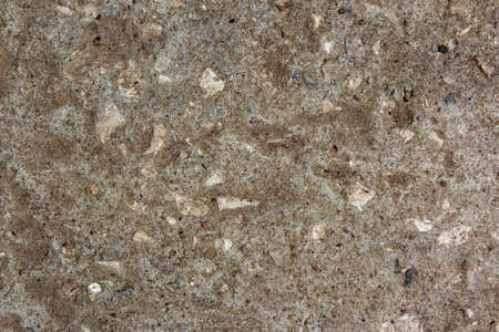 Muddy concrete wall with cracks and brown spots. Old and dirty tested wall background. Old cracked plaster. Architecture and construction works. Close-up old weathered concrete texture.