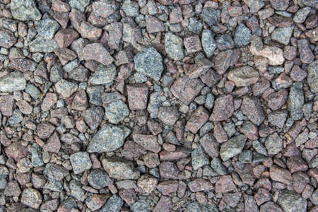 Gray gravel is used in the construction industry. Small road stone background. Granite gravel texture. Pattern of small gravel, rock or stone on the ground for background in grey vintage color tone.
