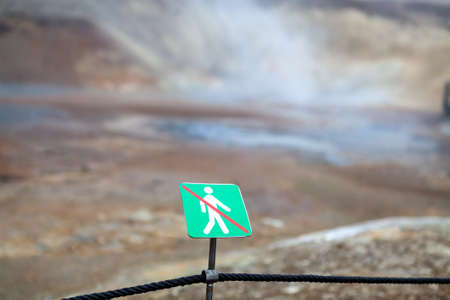 Warning sign of not crossing over rope fence. Big geyser. Geothermal area