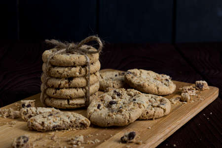 Light chocolate cookies, stacked and tied with a rope, pieces of light chocolate, on a dark wooden surface