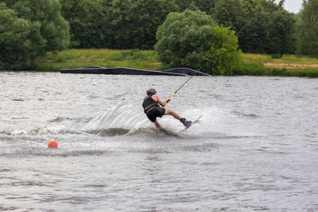 Wakeboarder on wakeboard landed in water surrounded by spray. A man rides water skis at high speed. Tense man wakeboarding in a lake. Wakeboarding is an extreme sport. Jumping from wave.