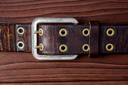 Old leather belt with a buckle on old wooden board. Mens brown belt made of genuine leather with a metal buckle on a dark background. Genuine leather, handmade. Metal rivet. 免版税图像