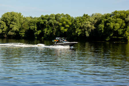 Modern speedboat sailing on forest background. Summer leisure and water activity. Rest On The River By Boat. Beautiful Motor Boat Rushes On The Water Surface Leaving Behind A Foam Trail