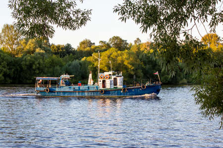 River tugboat is floating on the river. Trees grow on the banks of the river. Fork of the river. Landscape, summer day. Water excursions and trips. freight transport, copy space