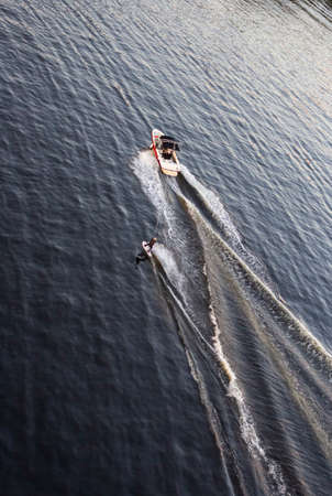 Speedboat towing an athlete on a Board against the background of the forest. Athlete water skiing and having fun. Speed boat for Surfing the Wakeboard. Water skiing on lake behind a boat. Top view