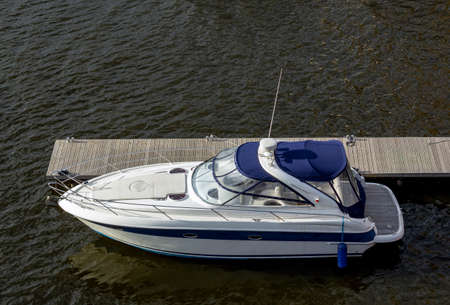 Pier speedboat. A marina lot. Yacht is moored at the quay. Marine parking of modern motor boats. Relaxation and fashionable vacation. Boats At The Marina. Top view Archivio Fotografico