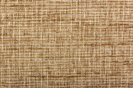 Factory fabric with brown and white threads interspersed. Close-up long and wide texture of natural fabric. Fabric texture of natural cotton or linen textile material.