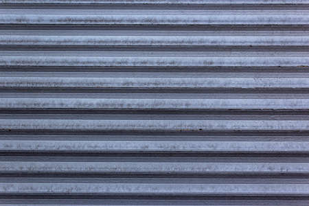 Corrugated sheet metal, badly painted with gray paint for background. Metal corrugated roofing sheet.Painting of metal surfaces for rust control Abstract background for sites and layouts. Iron fence