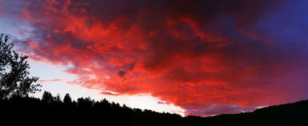 Sunset by a mountain in Quebec Canada with dramatic sky.