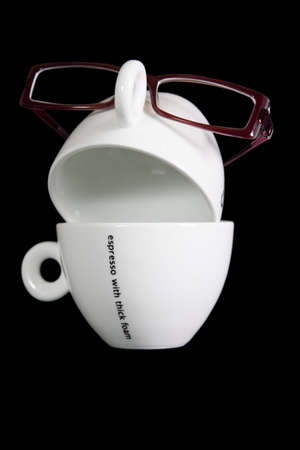 Two cups with glasses presenting a face calling for coffee.