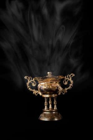 Egyptian hand made incense burner on a black background.  photo