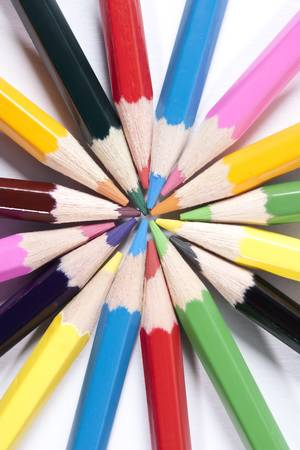 Colored pencils organized in a nice way looks like sun rays on a while isolated background.