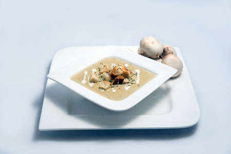 Hero Shot of a Mushroom Soup with bread crumbs, oregano on a minimal white background with a 45 degree angle