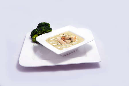 Hero Shot of a Broccoli Soup with bread crumbs, oregano on a minimal white background with a 45 degree front facing angle