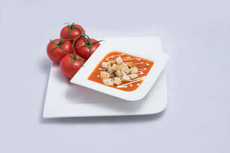 a Hero Shot of a Tomato Soup with bread crumbs, oregano on a minimal white background with a diagonal 45 angle