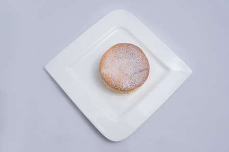 A low contrast Hero Shot of a pan cake on a plate, on a minimal white background with a diagonal 60 degree angle Stock Photo