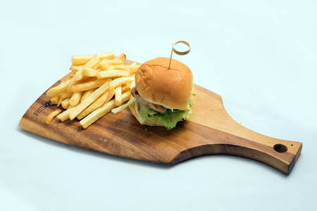 A low contrast Hero Shot of a grilled chicken slider burger, fries on a wooden platter board, on a minimal white background with a 45 degree angle from a diagonal perspective