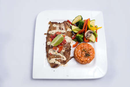 A Hero shot of a grilled fish fillet gratini with vegetables & lentils on the side, on a white plate, minimal background with a 60 degree front facing perspective.