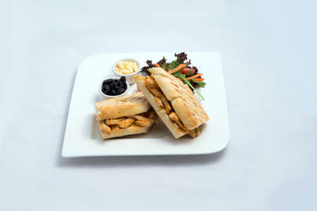 A low contrast Hero shot of a breakfast platter with grilled chicken panini sandwich with olives, cheese & vegetables- carrot, tomato, lettuce on a minimal white background with a 45 degree angle from almost front perspective