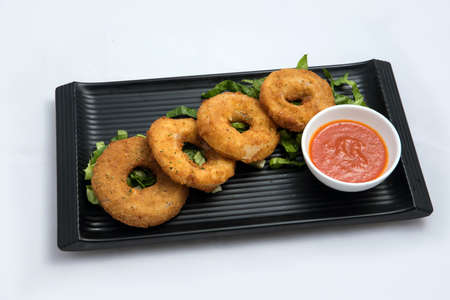 A low contrast Hero shot of an appetizer platter of onion rings with lettuce and tomato chutney on a minimal white background with a 45 degree angle front perspective