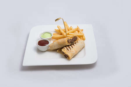 A low contrast Hero shot of a beef wrap sandwich with samurai & alger sauce and fries on the side, on a minimal white background with a 45 degree angle from front zoomed in perspective Stock Photo