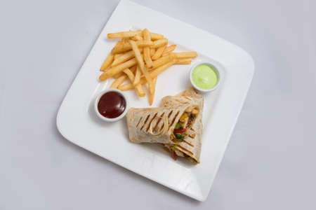 A low contrast Hero shot of a Chicken Pimiento sandwich with samurai & alger sauce & fries on the side, on a minimal white background with a 30 degree angle from diagonal perspective
