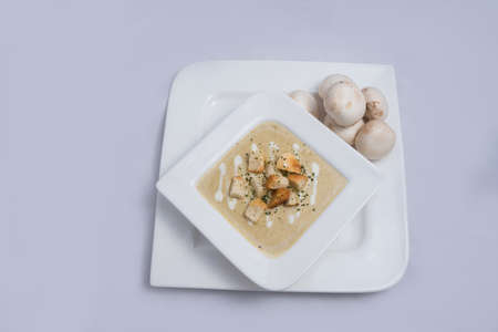 Contrasted Hero Shot of a Mushroom Soup with bread crumbs, oregano on a minimal white background with a 60 degree front facing angle