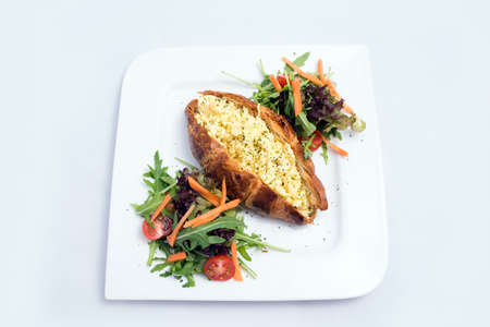 A low contrast image of a breakfast platter with egg-filled croissant with vegetables- carrot, tomato, lettuce on a minimal white background with a 30 degree angle from front perspective
