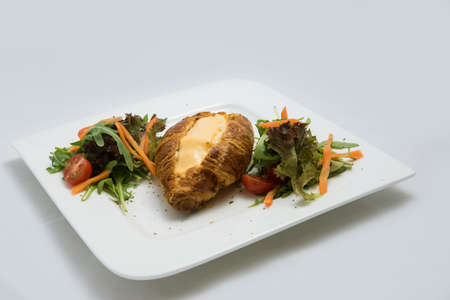 A low contrast image of a breakfast platter with cheese-filled croissant with vegetables- carrot, tomato, lettuce on a minimal white background with a 30 degree angle from front zoomed in perspective Stock fotó