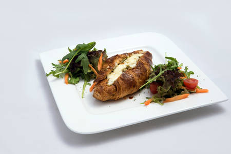 A low contrast Hero shot of a breakfast platter with cheese and zaatar filled croissant with vegetables- carrot, tomato, lettuce on a minimal white background with a 30 degree angle from front perspective Stock fotó
