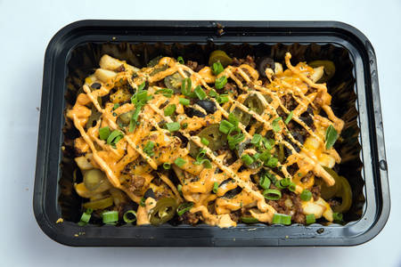 A high contrast Hero shot of a Take-Away Hot Loaded fries / chips with cheese, ground meat, olives, jalapeno, sauce & oregano, on a minimal white background with a 90 degree angle from zoomed vertical  perspective. Reklamní fotografie