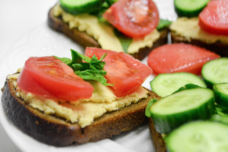 Whole grain bread toasts with classic lemon garlic hummus, cucumbers, spinach and tomatoes