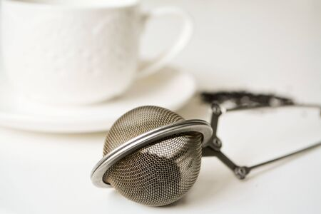 Zero waste tea drinking: white tea cup and loose leaf strainer spoon