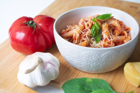 Classic italian penne pasta arrabbiata with its ingredients in the background: fresh tomatoes, basil, garlic and parmesan cheese