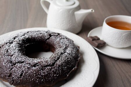 Chocolate cake with a hole in the center and sugar powder sprinkled on top, on the background are a teapot and tea cup with tea