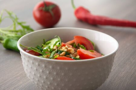 Healthy fresh summer salad with cucumbers, tomatoes, fresh arugula, chopped walnuts, pepper, olive oil and lemon juice on a rustic wooden surface