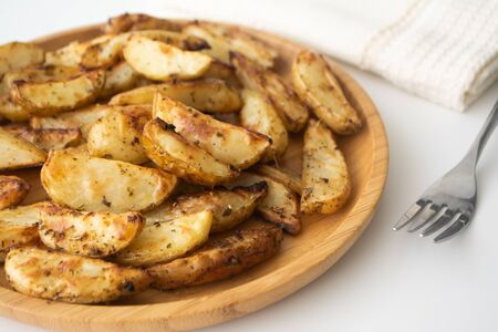 Oven baked potato wedges with dried herbs on a wooden plate with a napkin and a fork in the background Stock Photo