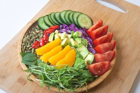 A buddha bowl of fresh summer healthy rainbow salad with cucumbers, tomatoes, arugula, basil, pumpkin seeds, avocado, red cabbage and chili pepper on a wooden surface