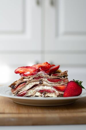 Light summer dessert: a slice of crepe layer cake with whipped cream, chocolate chips and strawberries between the layers. It is decorated with strawberries and placed on a white plate.