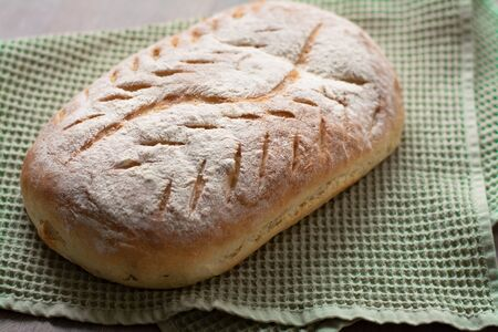 Homemade artisan sourdough bread loaf with artistic leaf pattern scoring and a wavy line in the middle on a green kitchen towel on wooden surface. Rustic aesthetic
