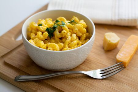 Traditional American macaroni and cheese comfort food (also called mac n cheese) with elbow pasta coated in a cheesy creamy cheddar sauce. Topped with parsley, cheese in the background.